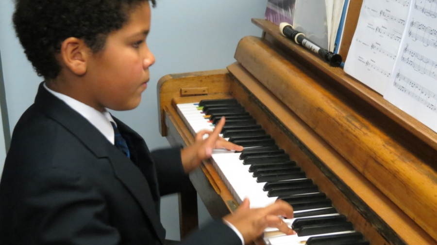 A young boy and the piano-js creative media..